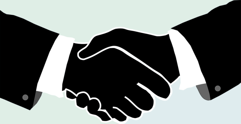 Two silhouetted hands shake on a light gray background. A jacket sleeve and shirtcuff are visible on each wrist, suggesting businessmen or politicians are doing the shaking.