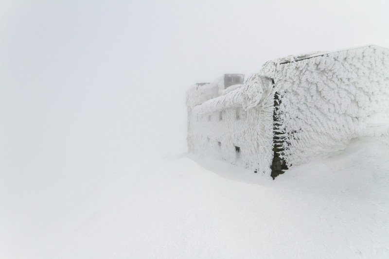 A blocky house, completely covered in spiky ice, stands against a snow-covered background.