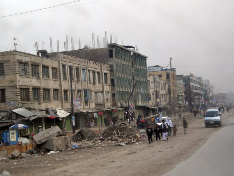 A dreary streetside scene in downtown Kabul. Concrete buildings and various detritus line a dusty road.
