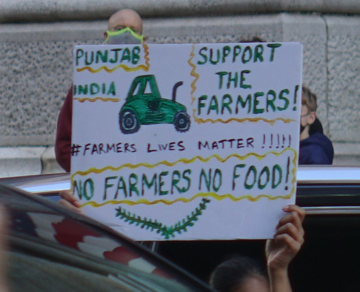 """A protest sign, decorated with a tractor and slogans like """"Support the farmers!"""" and """"No farmers no food!"""""""