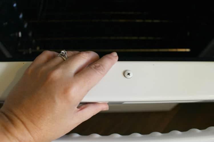 Accessing the top screws on the oven door.