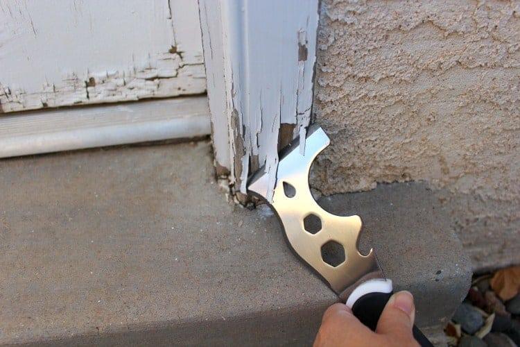 Painter's tool scrapes loose paint off door trim