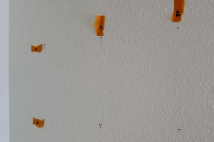 Labeling cross stitch mural grid with tape and pencil marks on wall