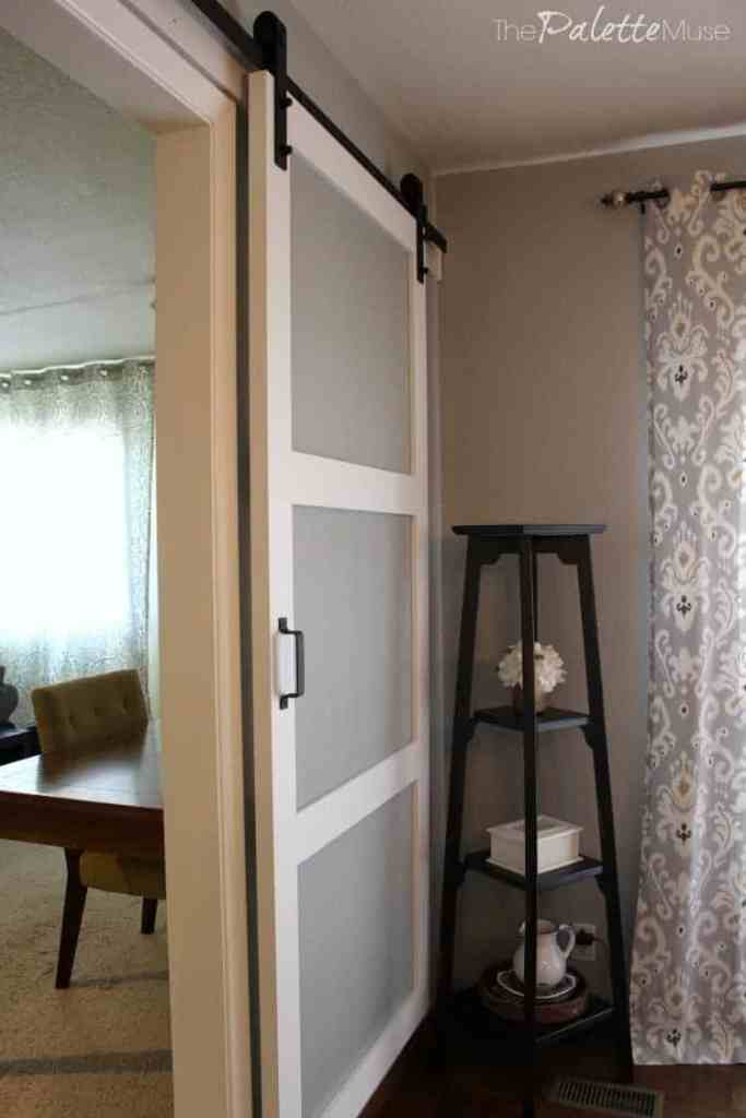 White barn door header matches the white trim throughout the room