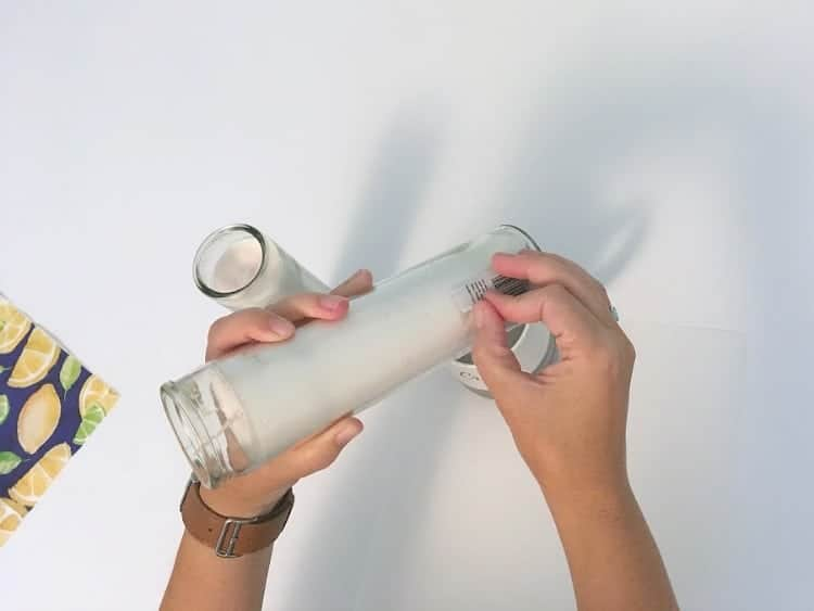 Peeling the label off a glass candle