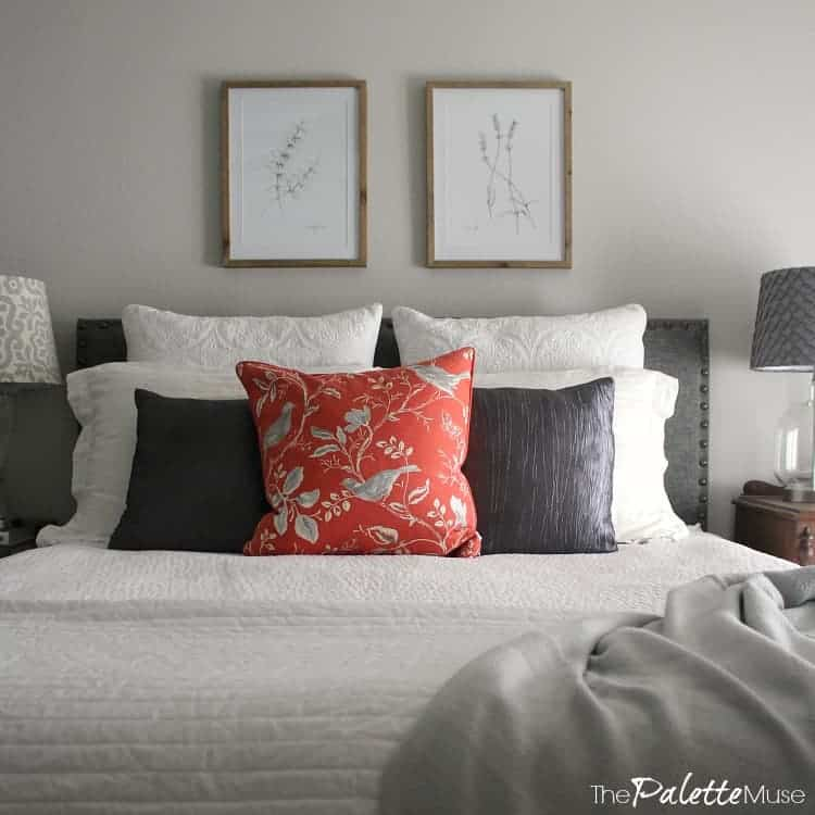 Bed with white and gray bedding, on gray wall with botanical drawings.