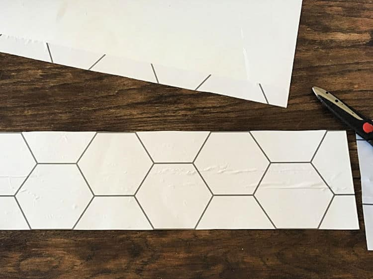 To make a hexagon stencil, apply a strip of the wallpaper to posterboard to use as your pattern.