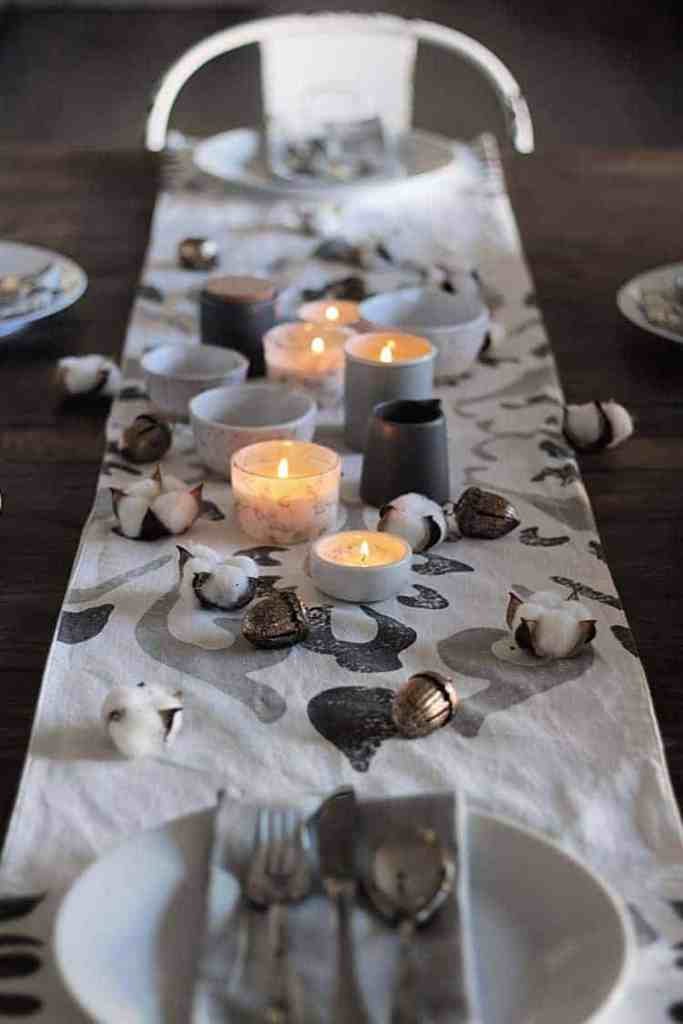 Simple Nordic Style Table Setting. Low candles, bronze acorns, cotton blossoms, and stoneware dishes on a white and gray table runner.
