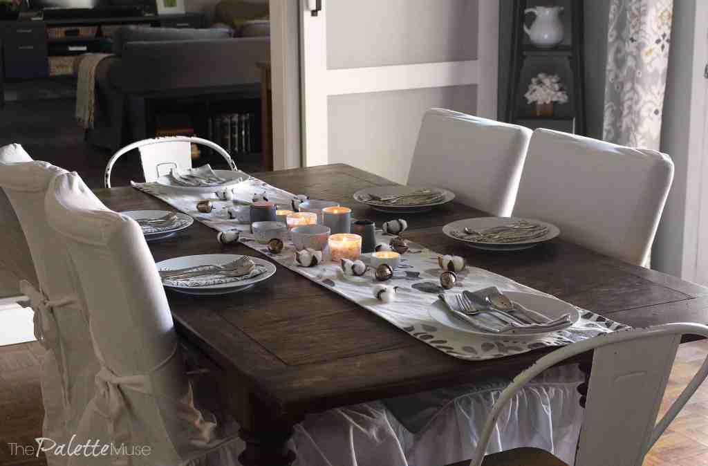 Dark wood table with white chairs, table runner, and dishes.