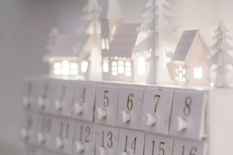 White wooden advent calendar topped with Christmas village and lights