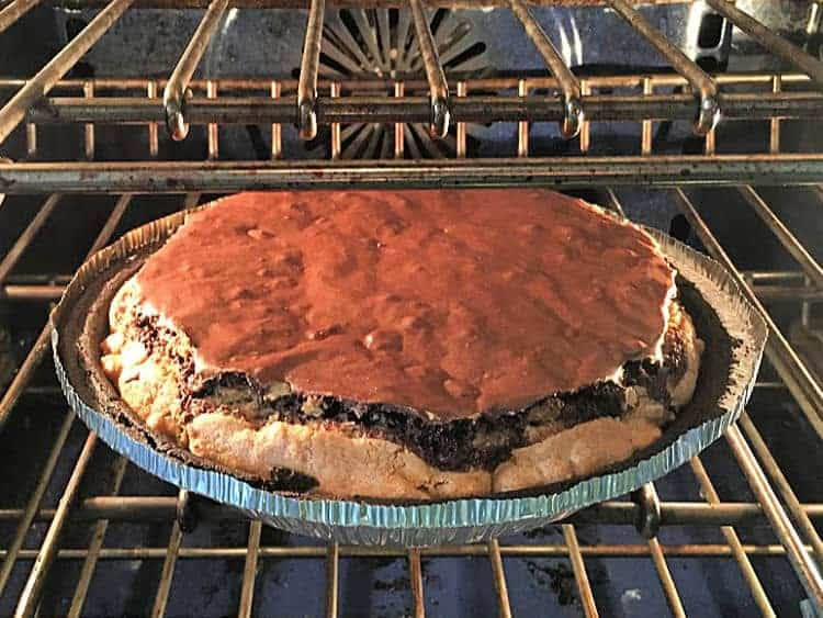 Chocolate brownie pie baking in oven, with brownie layer rising.