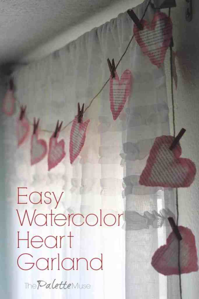 A pink heart garland made from book pages drapes over white window curtains
