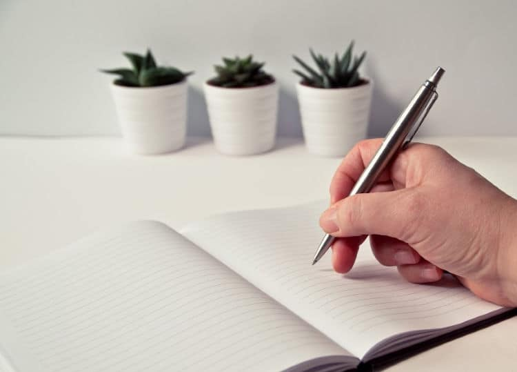 A blank notebook, with a person holding a pen, getting ready to start planning their remodel budget.