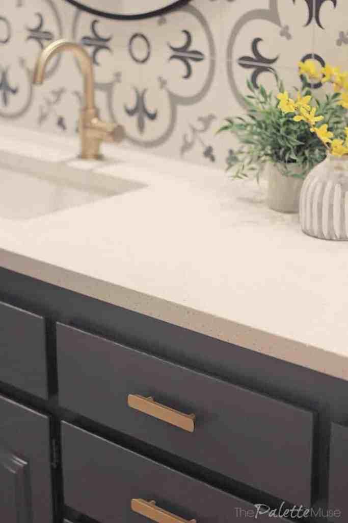 Brass drawer pulls on a dark gray bathroom vanity