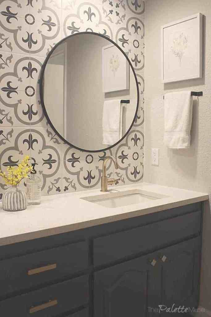 A patterned tile backsplash with brass fixtures and black accent pieces