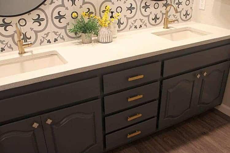 Brass cabinet hardware on a dark gray bathroom vanity