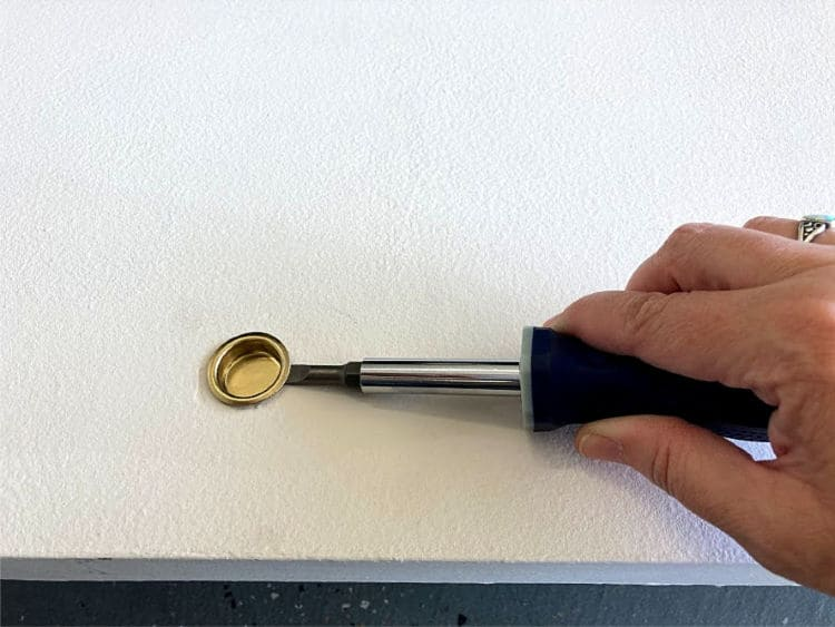 Using a screwdriver to pop out the small handle from a sliding closet door.