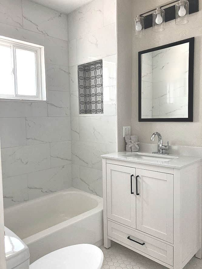 Small white bathroom with white vanity and white marble tile in the shower.