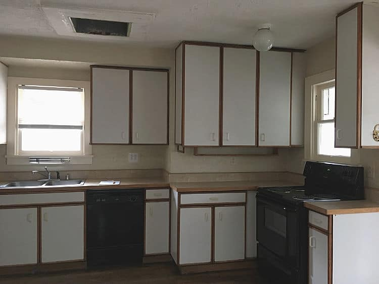 Kitchen with cheap white particle board cabinets and black appliances