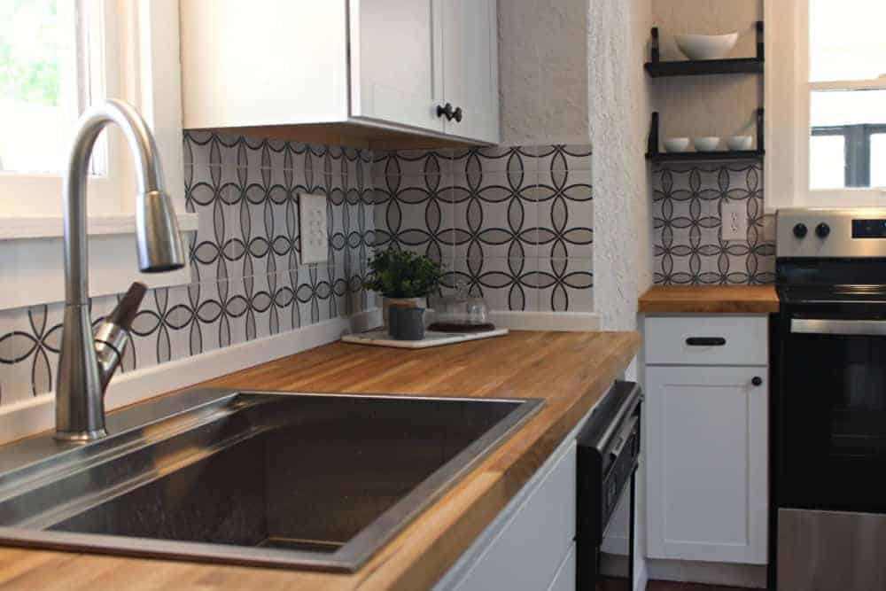 Kitchen detail with warm wood butcher block counter tops and geometric tile backsplash.