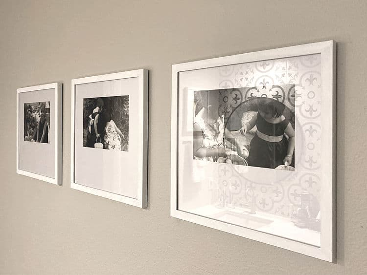 Three black and white photos in white frames, hung in a row