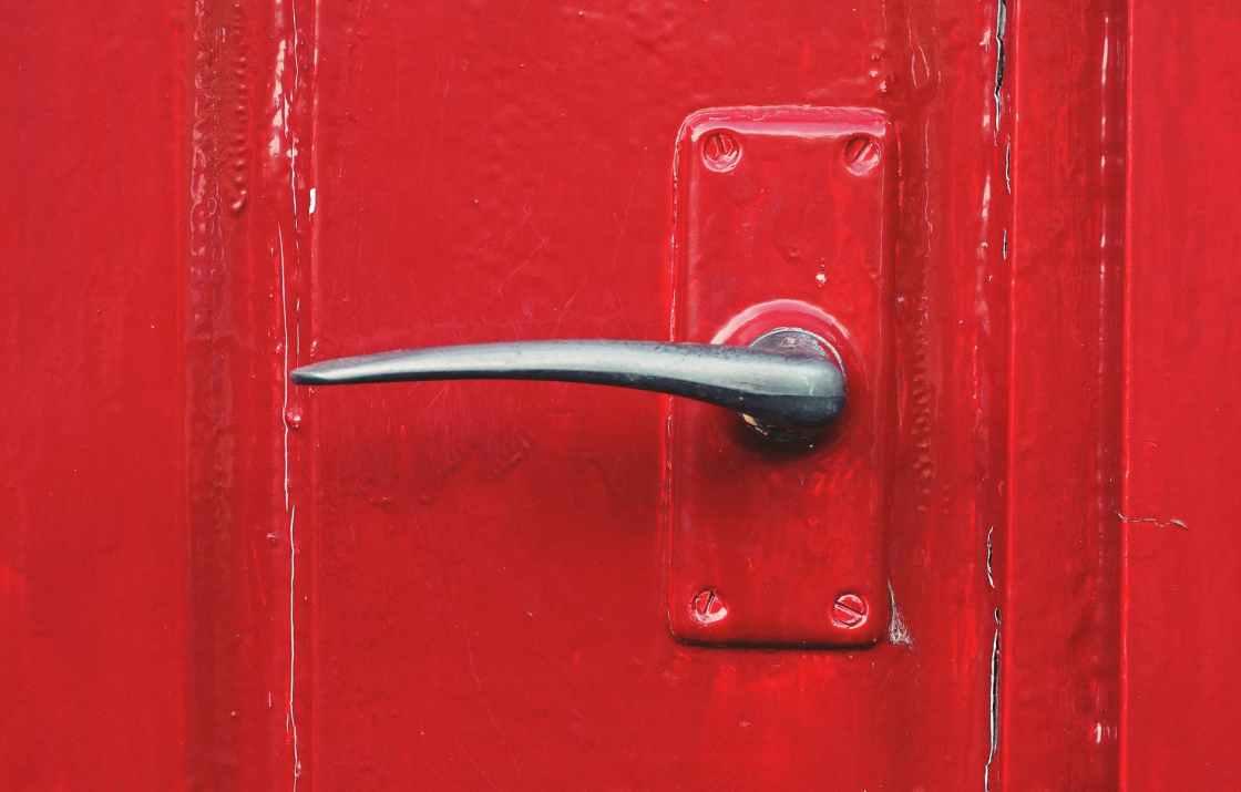 metal door handle on a red door
