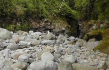 We climb over the rocks toward the river. That is the beginning of the canyon ahead. There is also a cave on the right.