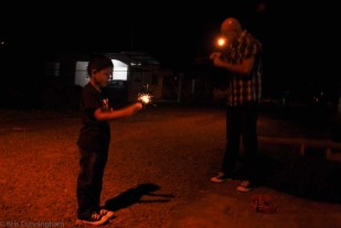 The grandson plays with sparklers with his dad as they wait for Santa.