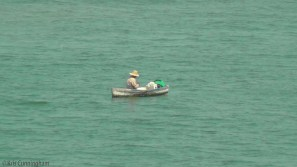 The man in the little boat is an interesting contrast to the gleaming white city.