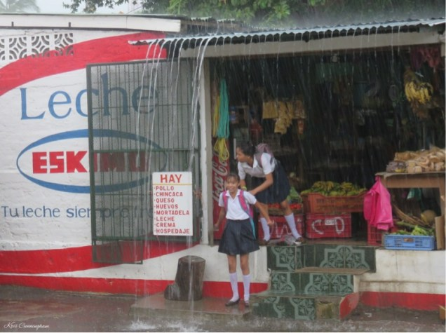 More girls in the rain. Everyone just waited in front of the supermarket where we were until the rain slowed down and then they went on their way. Since the rain is warm here people don't get too concerned about getting a little wet.