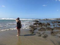 Karen surveys the scene with her bare feet in the wet sand.