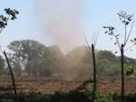 A dust devil blows across the field.
