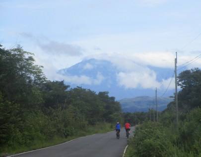 My friends bike ahead of me with Volcan Baru towering in front of them