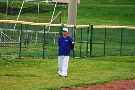 Varsity baseball coach Duane Higgs stands by the foul line to signal batters on what to do.