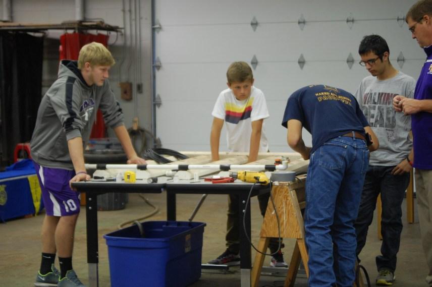 Senior Garrett Tolen, junior Logan Love, sophomore Zach Giles, freshman Wyatt Ashley and Mr. Scott work on an agriculture project that deals with plants and water.