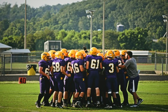 Rams varsity football players huddle up before the Forrest Park scrimmage.