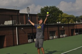 Senior Mason Deaton serves the ball during a home tennis match.