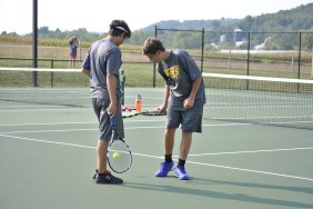Senior Mason Deaton talking to freshman Mason Buchanan during a home tennis match.
