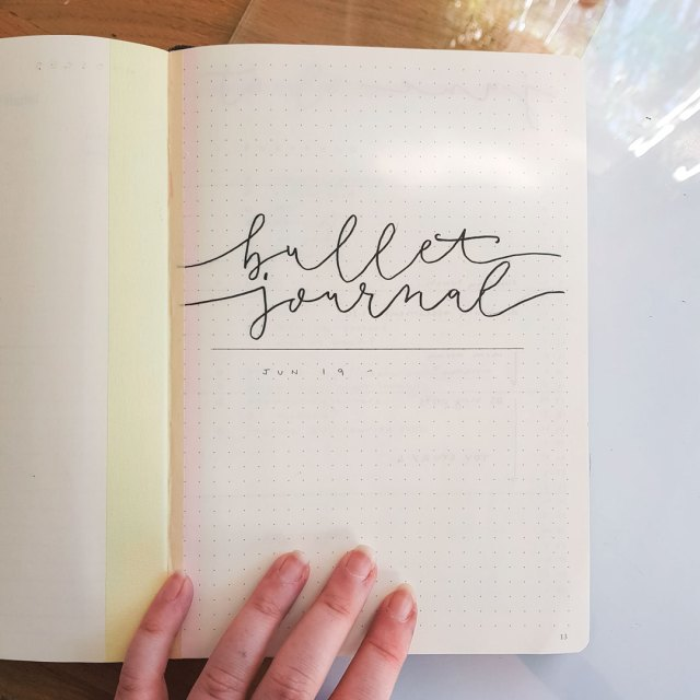 Cover page of a new bullet journal with script lettering which says bullet journal.