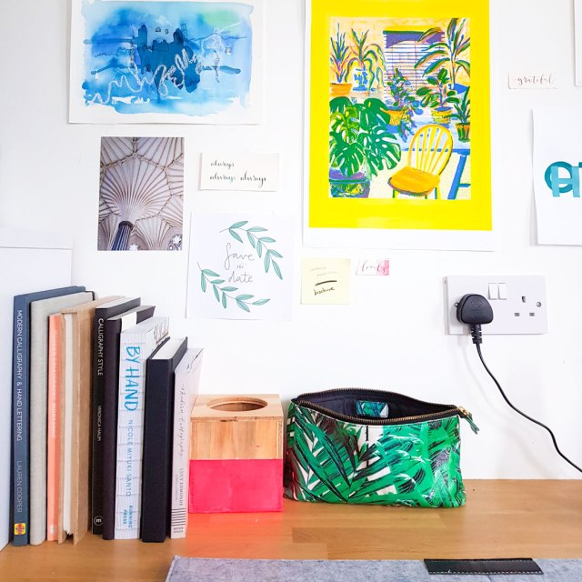 Image shows desktop with books and colourful posters on the wall.