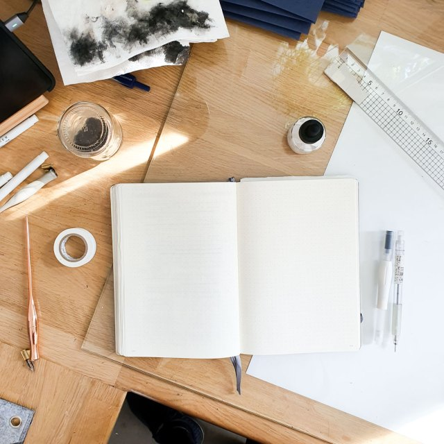 An open notebook lying on a desk surrounded by stationery items.