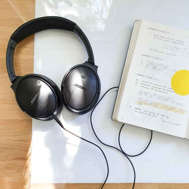 Image shows Bose noise cancelling headphones. How to create a productive workspace.