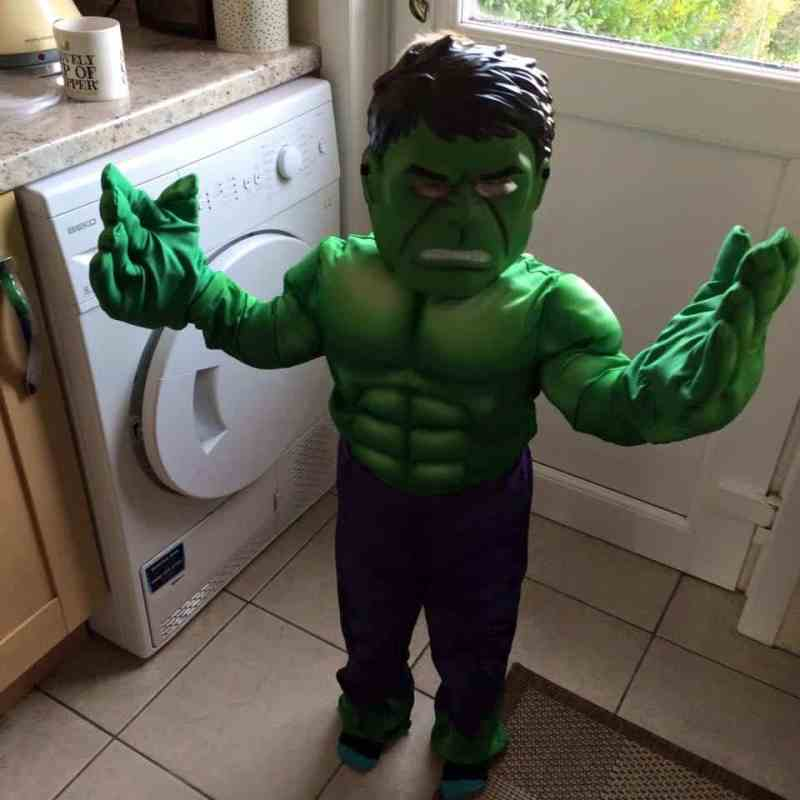 Child wearing a Hulk Superhero costume waving at the camera.