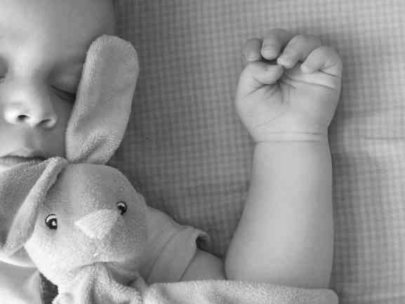 Close up photograph of baby asleep wit rabbit teddy