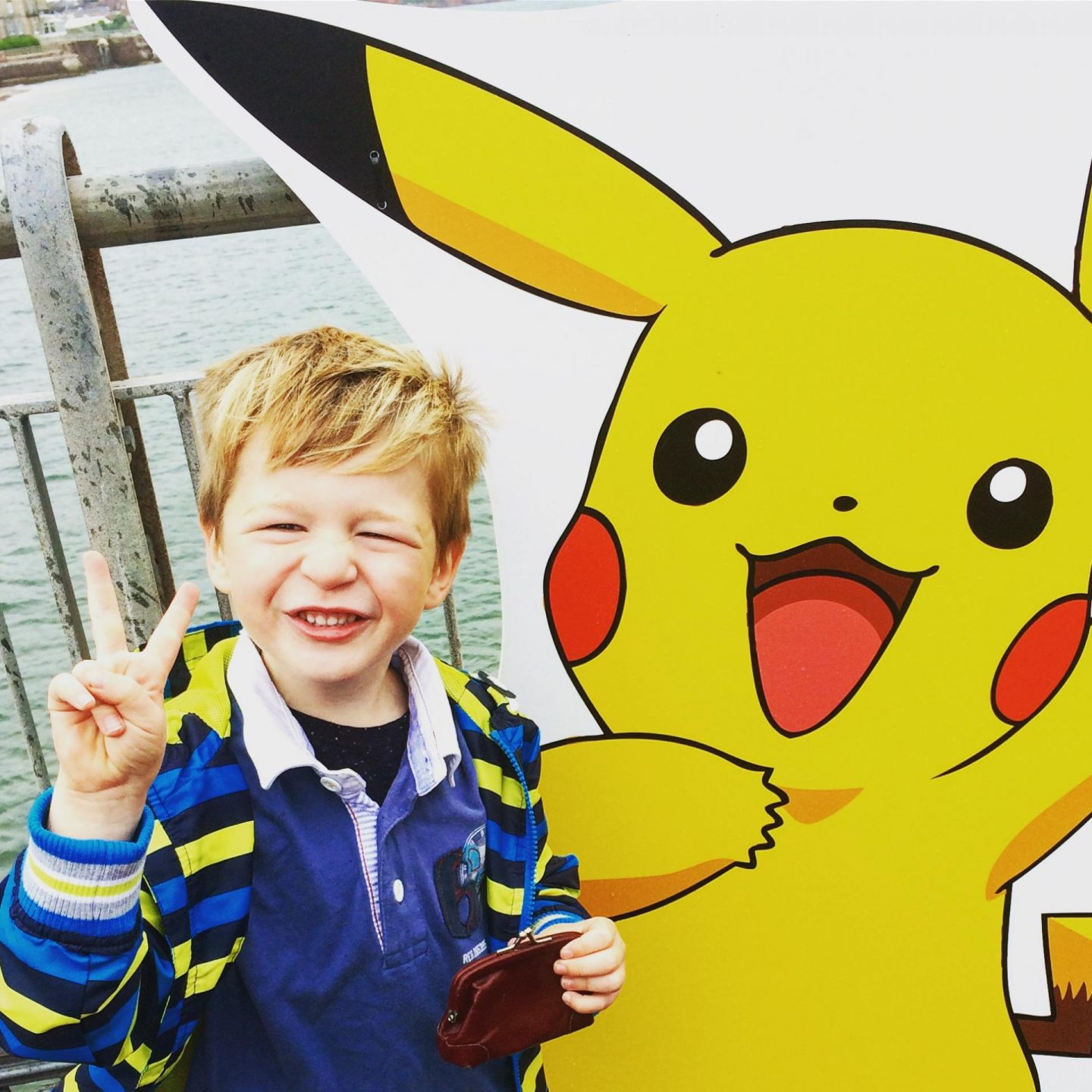 Little boy smiling waring a yellow coat infront of a large Picachu poster