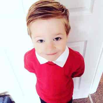 Little boy in a red school uniform smiling up at the camera with perfectly styled hair