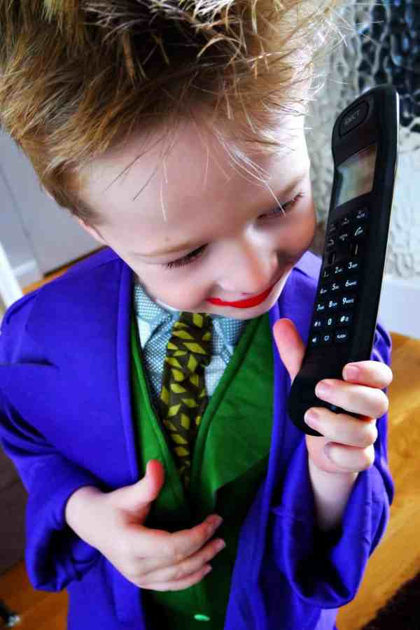 Little boy wearing lipstick talking on the phone