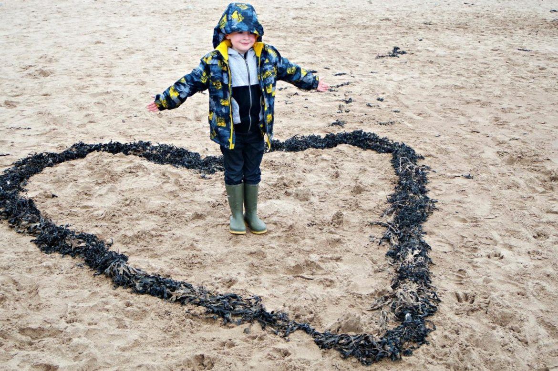 boy standing in seaweed heart