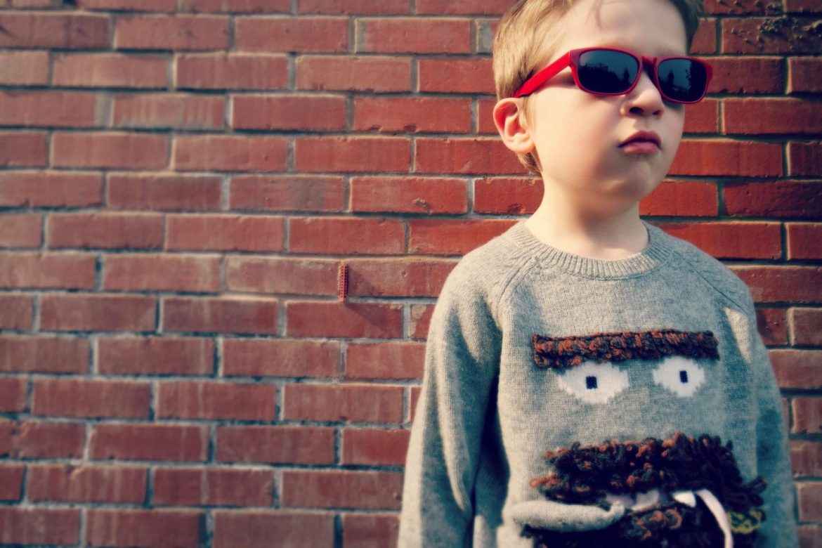 Little boy wearing red sunglasses standing infront of a brick wall