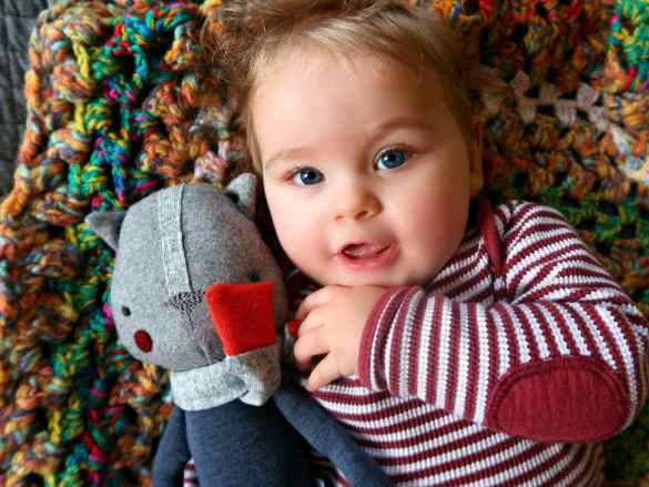 Baby in striped top holding teddy